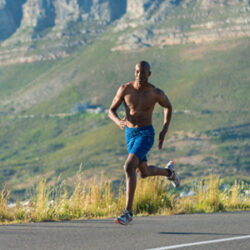Athletic, sporty, muscular, healthy black male running along a road outdoors with a mountain background.
